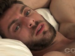 Hairy gay bear plays with his muscle dick on the bed