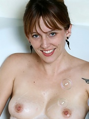 Alluring mature lady masturbates in a bathtub filled with bubbles