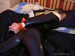 Latex-clad Brunette With An Awesome Body Tied Up On Her Bed